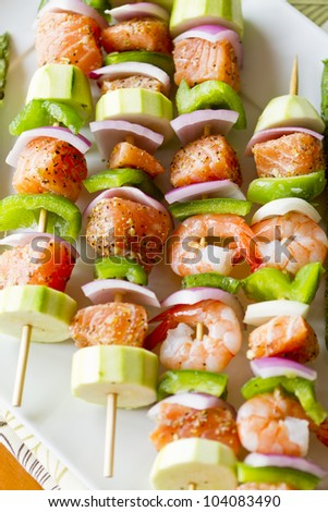 Salmon cubes and Shrimp complimented with vegetables on skewers. Ready to cook. Red onions, zucchini and green peppers. - stock photo