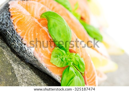 Salmon cuts on stone with basil and lemon