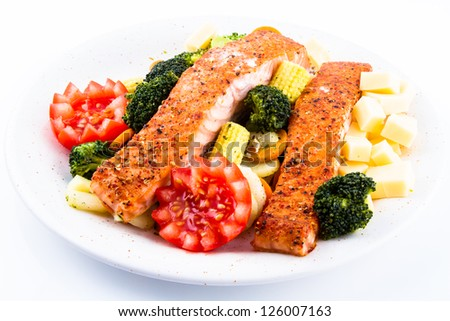 Salmon dinner with tomato, broccoli, corn and cheese on a white plate