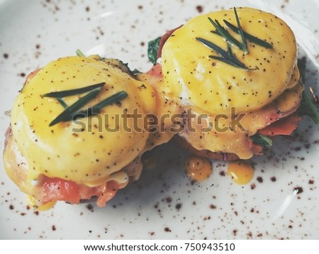 Salmon Egg Benedict on white plate and wood table ( above view)