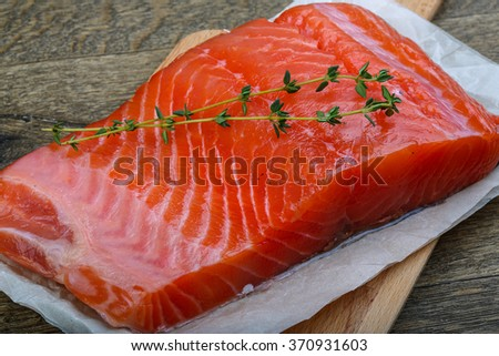 Salmon fillet served fresh thyme branch on wood