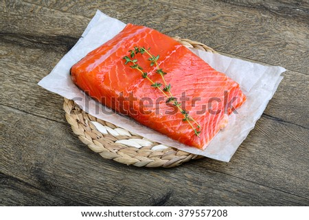 Salmon fillet served fresh thyme branch on wood - stock photo