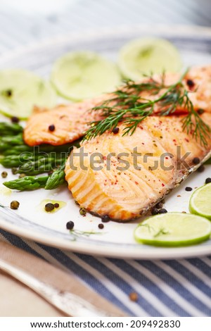 salmon fillet with asparagus in a dish with a blue border and a blue stripe placemat