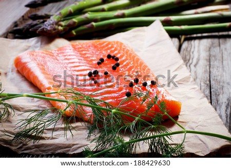Salmon fillet with asparagus on table - stock photo
