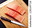 salmon fillet with knife on wood board - stock photo