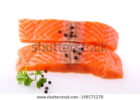 Salmon fillet with pepper and parsley over white selective focus - stock photo