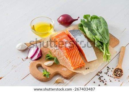 Salmon fillet with spinach, salt, pepper, garlic, oil, white wood background