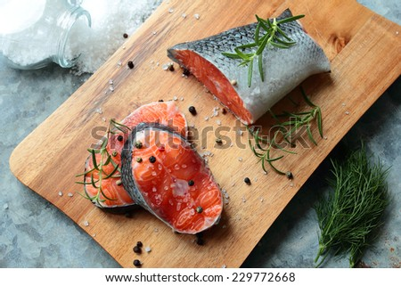 Salmon fillets on wooden board with fresh spices - stock photo