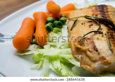 Salmon fillets served on a plate with mixed salad - stock photo
