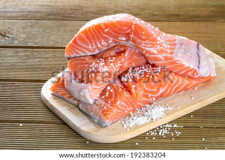 Salmon fillets with salt on a wooden background - stock photo