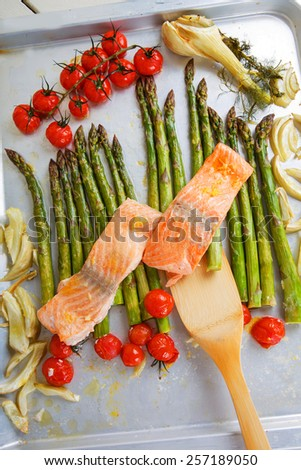 Salmon fish and vegetables: green aspargus, cherry tomatoes and fennel, on oven tray - stock photo
