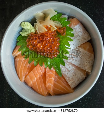 Salmon Ikura Don with wasabi and ginger or salmon rice bowl on the black table, Japanese food - stock photo