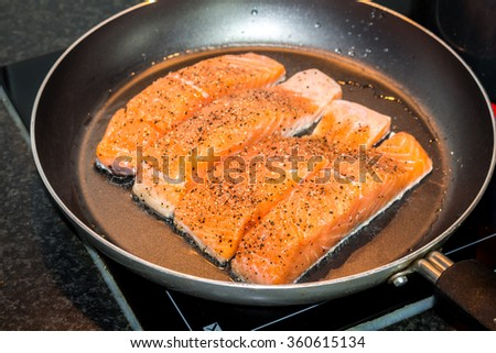 Salmon in pan - stock photo