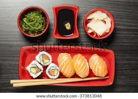 Salmon nigiri sushi on plate with chopsticks