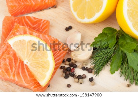 Salmon on cutting board with lemons and herbs. Closeup - stock photo