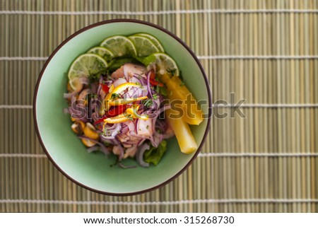 Salmon peruvian ceviche, with purple onion on bamboo mat. Served with pineapple and lime. - stock photo