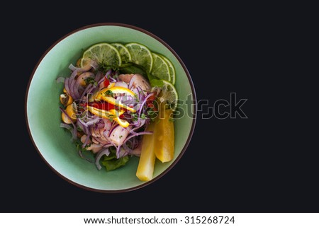 Salmon peruvian ceviche, with purple onion on black background. Served with pineapple and lime. - stock photo