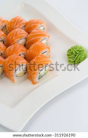 Salmon (philadelphia) sushi roll on a white plate with ginger and wasabi - stock photo