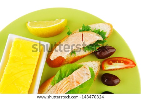salmon pieces on baguette slices with butter and olives