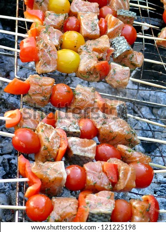 salmon pieces on skewers on grill with vegetables - stock photo