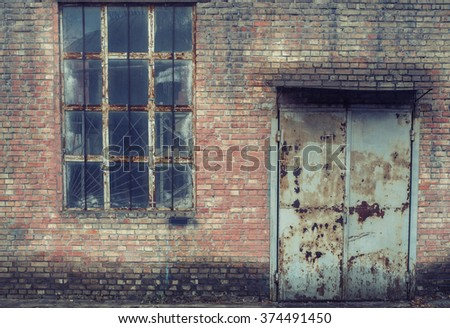 Salmon pink brick industrial building wall with rusty door and aged window. Vintage effect.  - stock photo