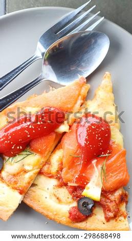 Salmon Pizza two slices ready to eat. - stock photo