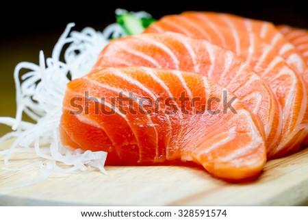 Salmon raw sashimi on wooden table - stock photo