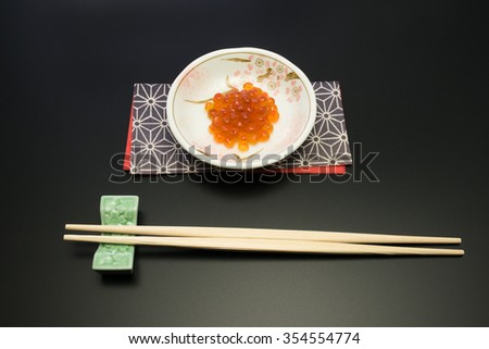 salmon roe and chopsticks. in Japan, salmon roe is called as Ikura and recognized as one of the luxury food stuffs. it is served for the festive meals such as New Year celebration dish. - stock photo
