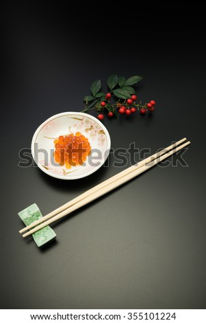 salmon roe and chopsticks. in Japan, salmon roe is called as Ikura and recognized as one of the luxury food stuffs. it is served for the festive meals such as New Year dishes.  - stock photo
