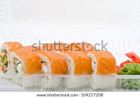 Salmon rolls in plastic container. Sushi delivery - stock photo