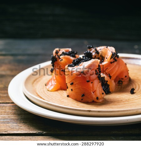 Salmon rolls with black caviar, served on ceramic plate on old wooden table. Square image - stock photo