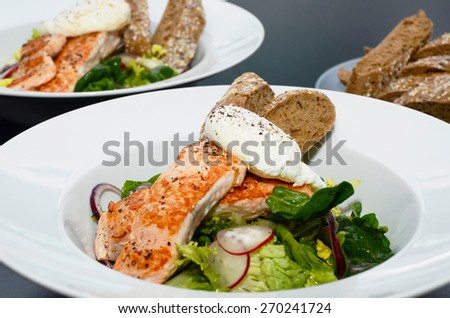Salmon Salad with Egg Benedict, served with baguette - stock photo