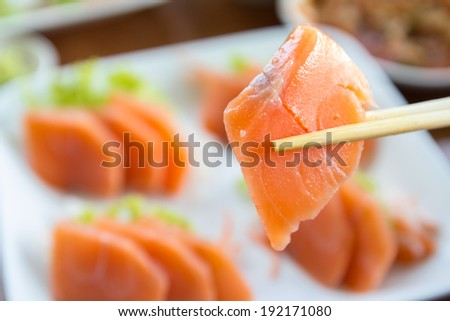 Salmon sashimi on white dish, food background