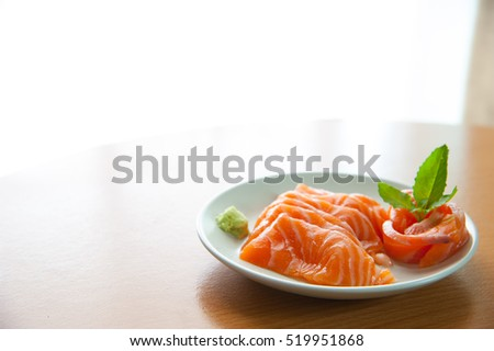 Salmon sashimi on wooden table in right