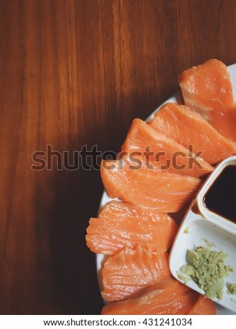 Salmon sashimi set in white dish also see soya source and wasabi together. All put on a wooden floor background. Vintage filter. - stock photo