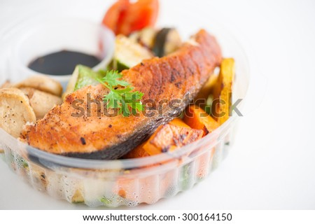 Salmon steak and grilled vegetables cooked by clean food concept with Japanese sesame soy sauce in lunch box