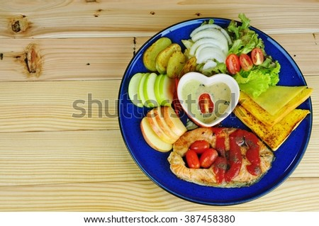 Salmon steak with breads, potato slice, green apple slice, red apple slice, onion slice and cabbage salad in blue plate on the wooden background - stock photo