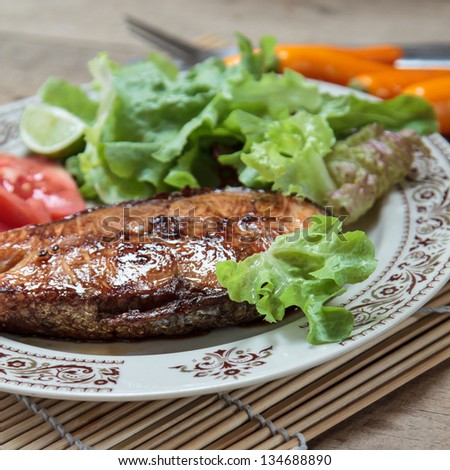 salmon steak with lime on white plate