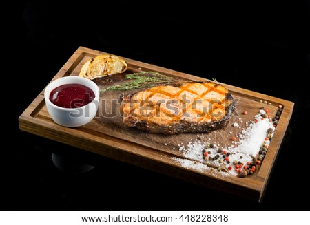 Salmon steak with sauce on the board