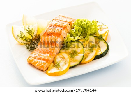 Salmon steak with sliced zucchini and courgette, lettuce and lemon garnished with fresh dill for a tasty seafood platter or appetizer - stock photo