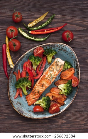 Salmon steak with vegetables om ceramic plate - stock photo