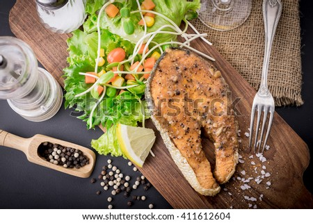 salmon steak with vegetables on woodden board. - stock photo