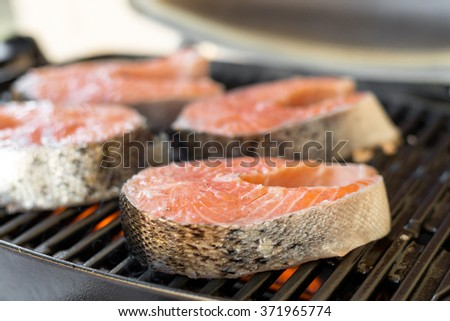 Salmon steaks barbeque cooking on grill - stock photo