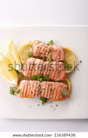 salmon steaks in a buttered grilled with lemon