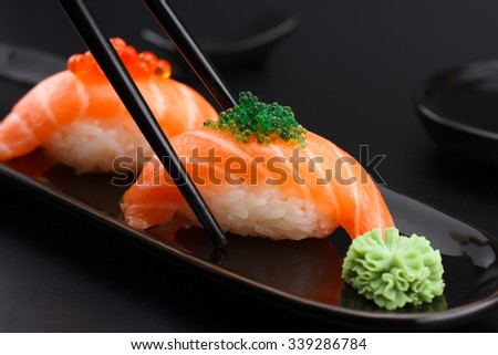 Salmon sushi nigiri in chopsticks over black background - stock photo
