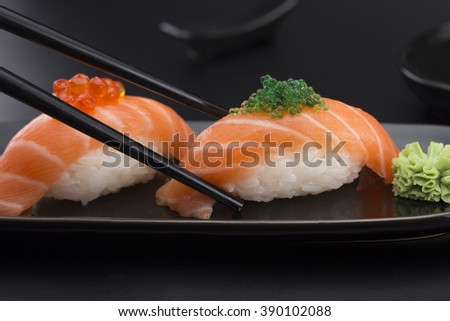 Salmon sushi nigiri in chopsticks over black background