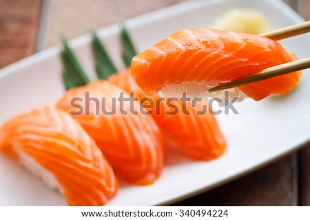Salmon Sushi on the white plate on a wooden table.