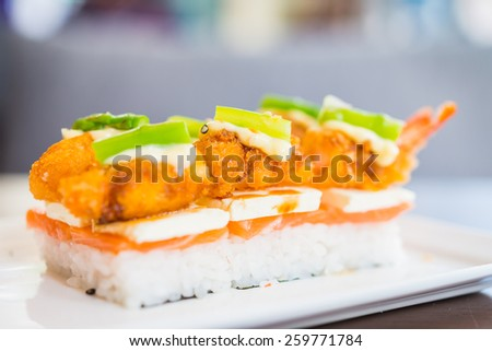 Salmon sushi with tempura fried shrimp and cheese on top in white plate on wooden table - stock photo