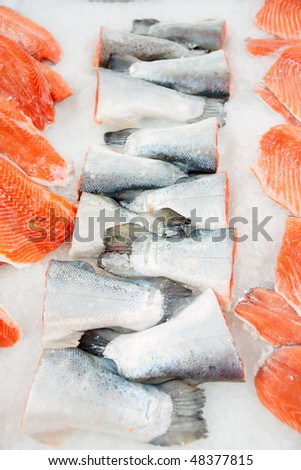 Salmon tails and fillet on cooled market display in supermarket - stock photo