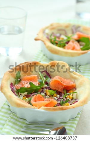 Salmon tarte flambee with arugula and onion